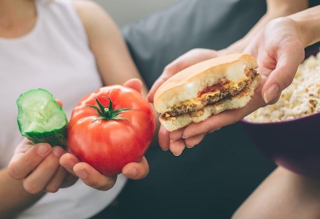 Donne in possesso di hamburger, pomodoro e cetriolo