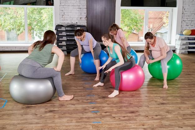 Donne incinte che allungano nella lezione di fitness