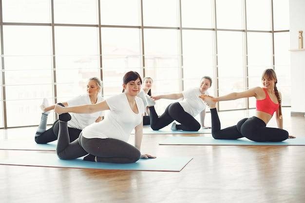 Donne incinte che fanno yoga con un allenatore