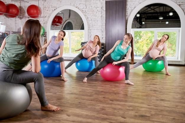 Donne incinte che si esercitano nella classe di forma fisica