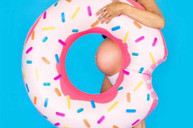 Donne incinte felici in costume da bagno con la ciambella dell'anello di nuoto su una parete blu colorata
