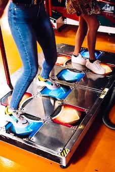 Donne laterali che giocano a ballo arcade