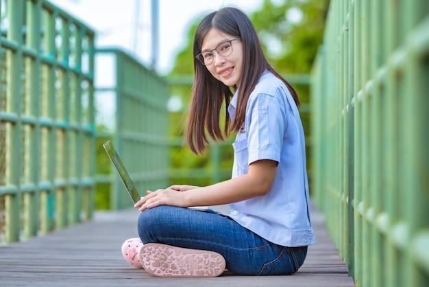 Donne lavoratrici asiatiche in parco pubblico facendo uso dello stile di vita moderno del computer portatile e dello smartphone, donne lavoratrici asiatiche che lavorano a casa