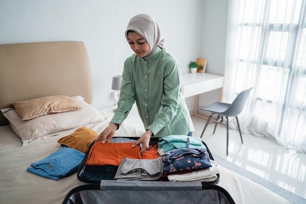 Donne musulmane che indossano l'hijab preparando la valigia