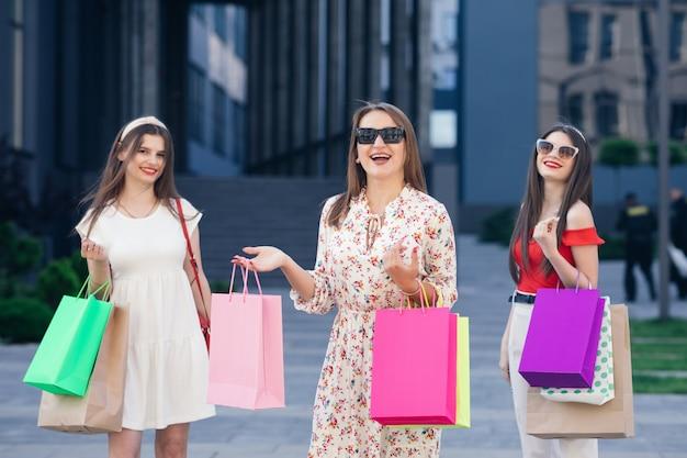Donne nello shopping. ragazze giovani con borse della spesa colorate in giro per la città dopo lo shopping. consumismo, acquisti, shopping, concetto di stile di vita.