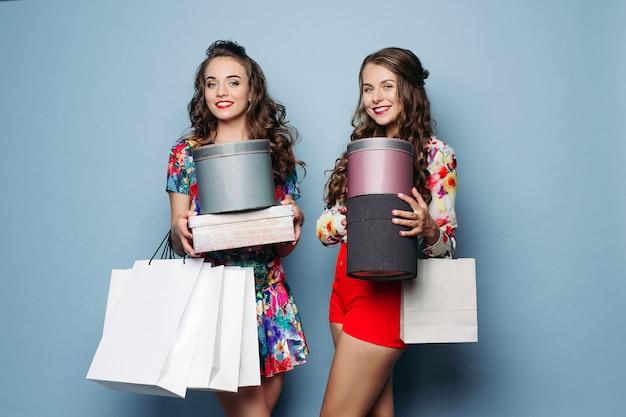 Donne piuttosto alla moda con un sacco di borse per la spesa e borsa per cappelli