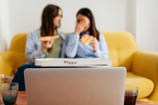 Donne rilassanti con pizza e laptop