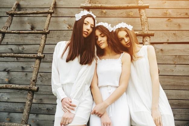 Donne rilassato con abiti bianchi e scale in legno di fondo