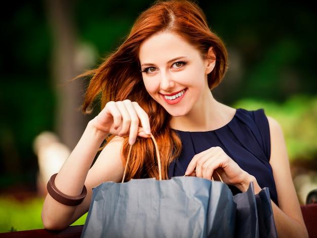 Donne rosse di stile che si siedono sul banco con i sacchetti della spesa