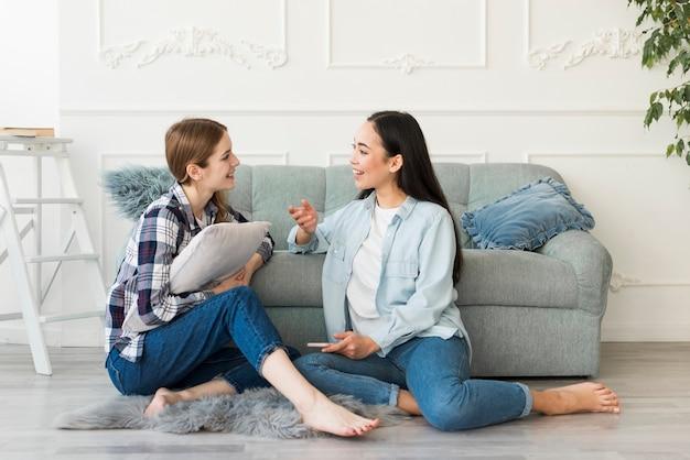 Donne sedute sul pavimento a piedi nudi e parlando animatamente