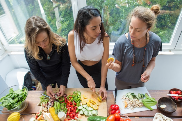 Donne seri che chiacchierano e che tagliano le verdure in cucina