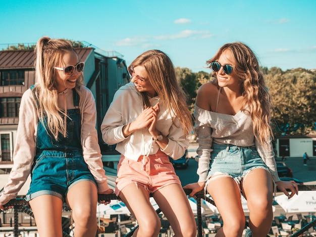 Donne sexy che si siedono sul corrimano in strada comunicano e discutono di qualcosa