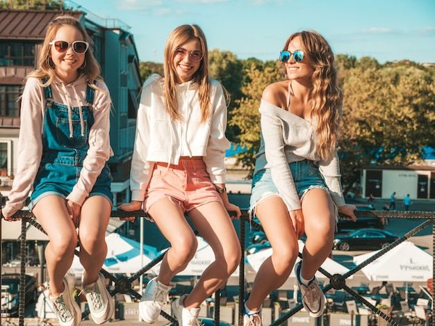 Donne sexy che si siedono sul corrimano in strada. modelli positivi che si divertono in occhiali da sole. comunicano e discutono di qualcosa