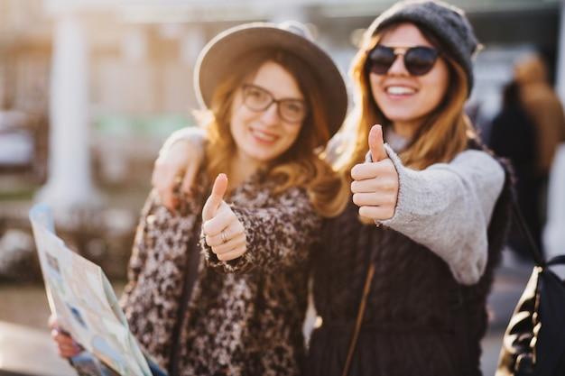 Donne sorridenti alla moda del ritratto che esprimono emozioni luminose in giornata di sole in città. buon viaggio insieme, bei momenti di gioiosi toutisti, look elegante, vacanza, felicità.