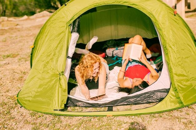 Donne sorridenti che leggono i libri in tenda