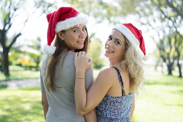 Donne sorridenti che portano i cappelli di santa e che girano nel parco