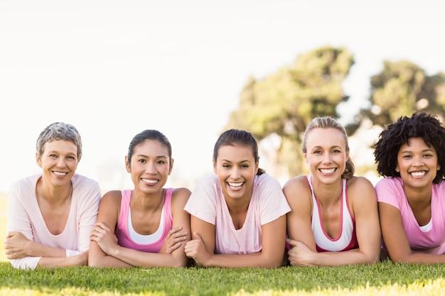 Donne sorridenti che si trovano in una fila e che indossano rosa per il cancro al seno