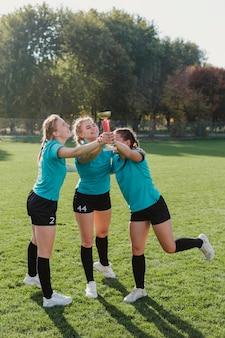 Donne sorridenti che tengono un trofeo di calcio