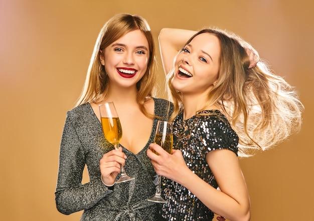 Donne sorridenti felici in eleganti abiti glamour con bicchieri di champagne sul muro d'oro