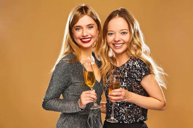 Donne sorridenti felici in eleganti abiti glamour con bicchieri di champagne