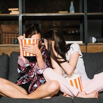 Donne spaventate che si siedono sul sofà che nasconde la loro faccia