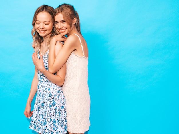 Donne spensierate sexy che posano vicino alla parete blu. divertirsi e abbracciarsi