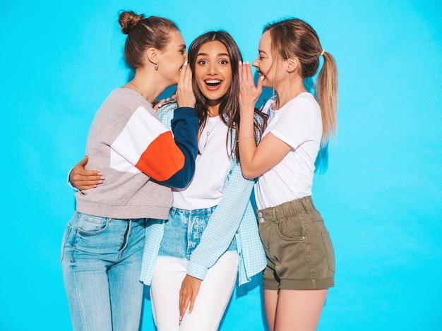Donne spensierate sexy che posano vicino alla parete blu in studio. modelle positive che impazziscono e si divertono. condividi segreti, pettegolezzi