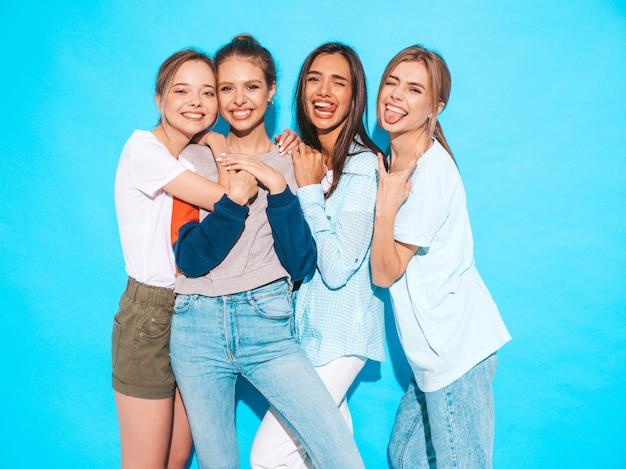 Donne spensierate sexy che posano vicino alla parete blu in studio. modelle positive che si divertono e abbracciano. mostrano lingue