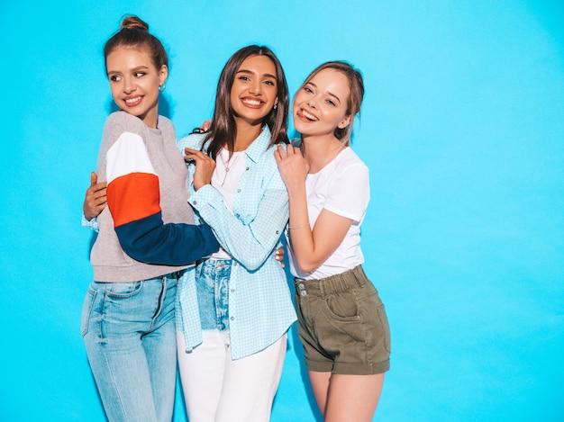 Donne spensierate sexy che posano vicino alla parete blu in studio. modelli positivi che si divertono e si abbracciano