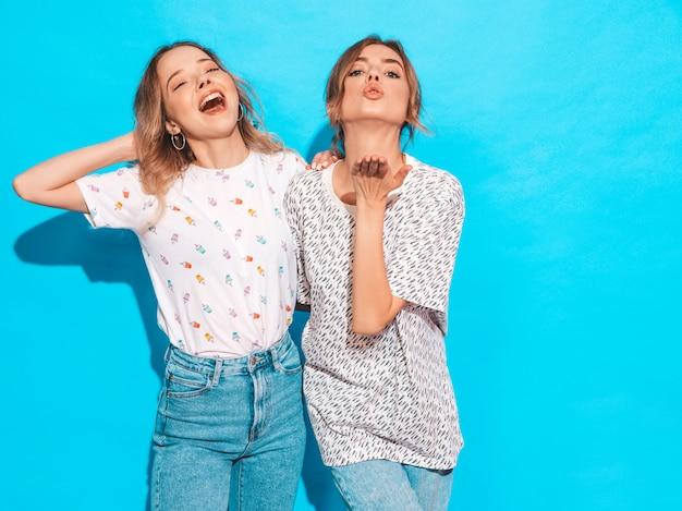 Donne spensierate sexy che posano vicino alla parete blu. modelle positive che si divertono e mostrano una smorfia divertente