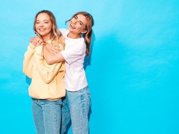 Donne spensierate sexy che posano vicino alla parete blu. modelli positivi che si divertono