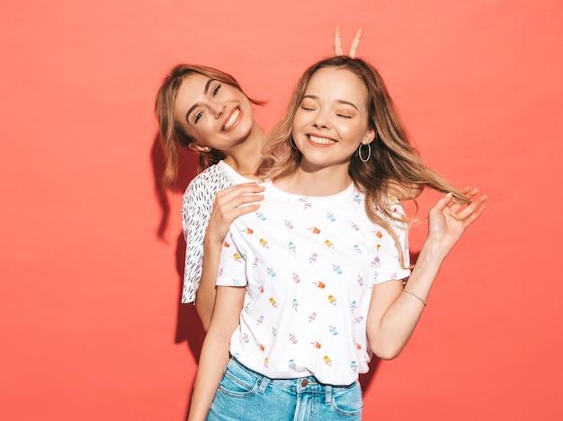 Donne spensierate sexy che posano vicino alla parete rosa. modelli positivi che si divertono