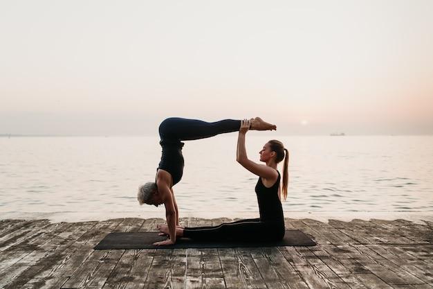 Donne sportive che fanno yoga asana con verticale su alba vicino al mare