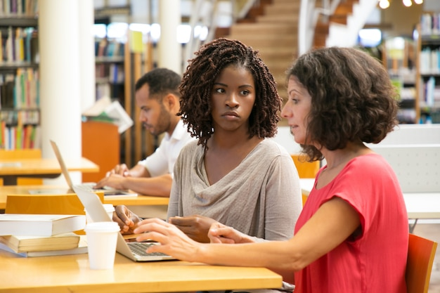 Donne stanche che per mezzo del computer portatile alla biblioteca