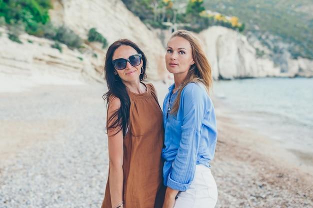 Donne sulla spiaggia godendo le vacanze estive guardando il mare