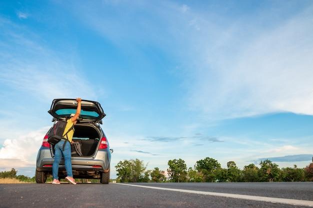 Donne turisti con i suoi viaggi sulla strada durante il viaggio