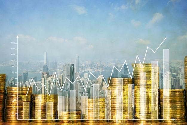 Doppia esposizione della pila della moneta con il grafico e la città finanziari