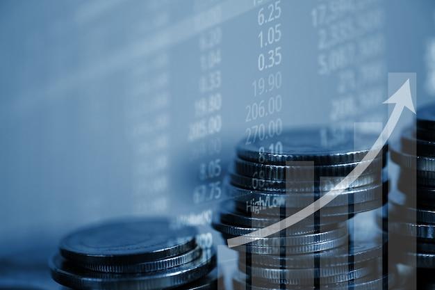 Doppia esposizione della pila di monete con schermo del mercato azionario
