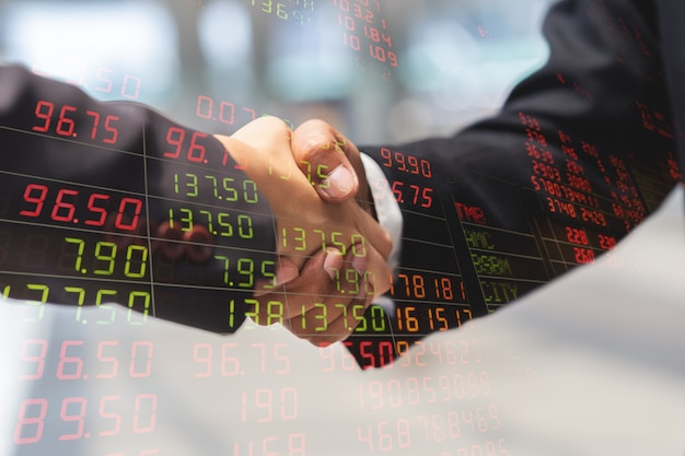 Doppia esposizione della stretta di mano dell'uomo d'affari e della donna di affari per il grafico dell'indicatore di prezzi e del partner dal mercato azionario, concetto di affari.