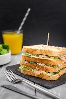 Doppio sandwich su ardesia con posate