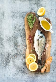 Dorado crudo fresco o pesce dell'orata con il limone, le erbe, l'olio e le spezie sul bordo di legno rustico sopra la parete di lerciume