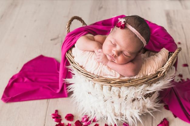 Dormire bambino tenero sotto coperta rosa
