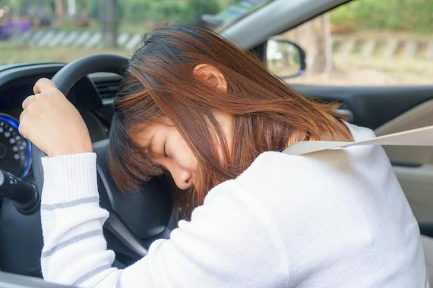 Dormire, stanco, chiudere gli occhi giovane donna alla guida della sua auto dopo una lunga gita di un'ora