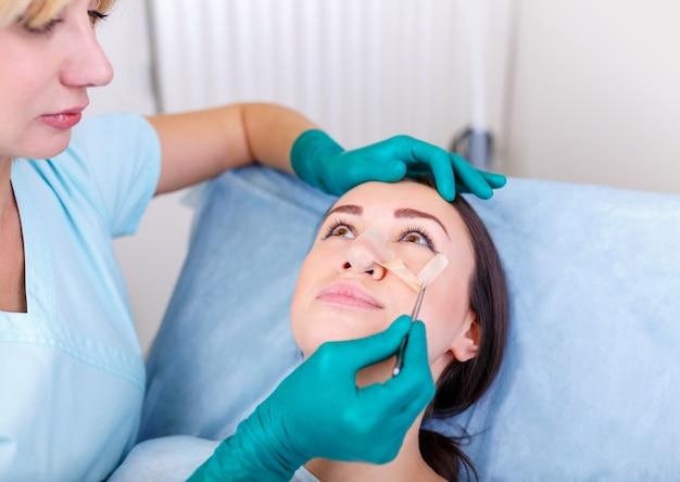 Dottore che controlla il viso della donna, dopo la chirurgia plastica, la rinoplastica, la blefaroplastica.