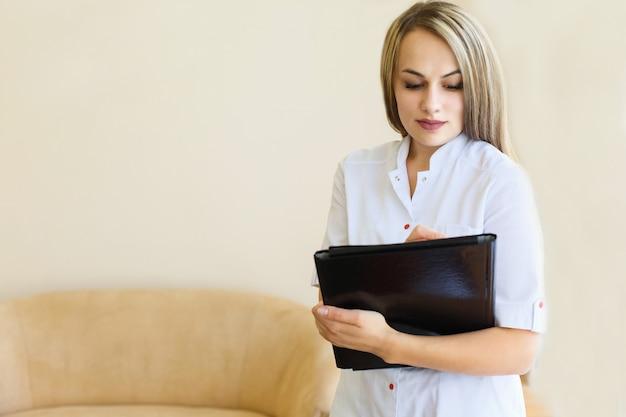 Dottore femminile con una cartella nera in piedi uniforme.