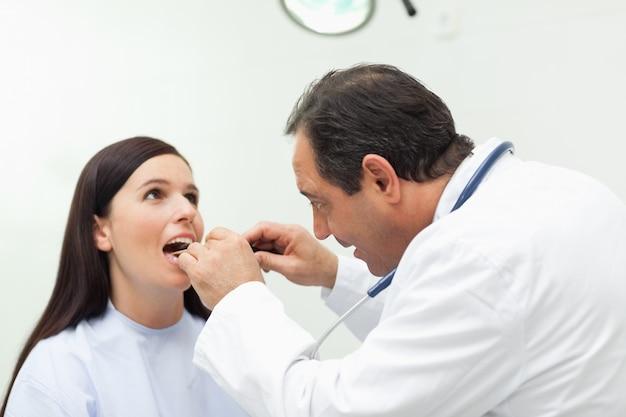 Dottore guardando la bocca del suo paziente