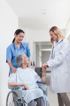 Dottore guardando un paziente su una sedia a rotelle