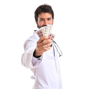 Dottore holding pillole su sfondo bianco