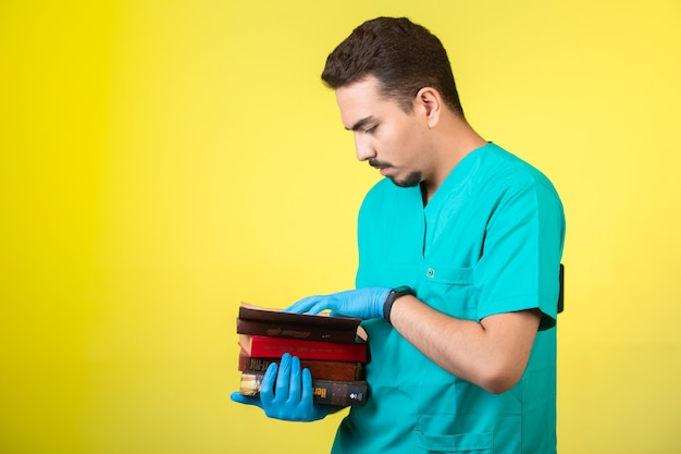 Dottore in uniforme e maschera a mano che tiene libri e pratica.