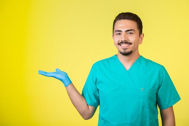 Dottore in uniforme e maschera per le mani con una mano aperta sopra.
